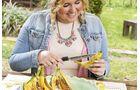 Dann müssen die Bananen der länge nach eingeschnitten werden und mit den Schokoriegelstücken befüllt werden.